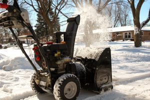 Clearing snow from sidewalks with snowblower.